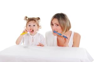 mother teaching daughter to brush her teeth